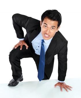 Portrait d'homme d'affaires grimper au mur