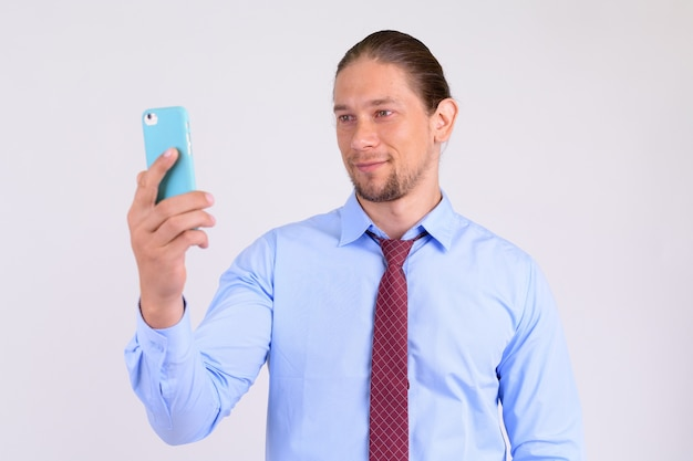 Portrait d'homme d'affaires heureux à l'aide de téléphone contre backgrou blanc