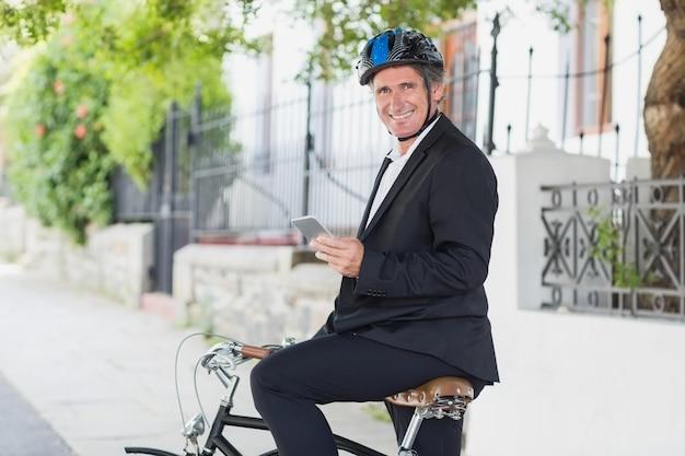 Portrait d'homme d'affaires heureux à l'aide de téléphone portable à vélo