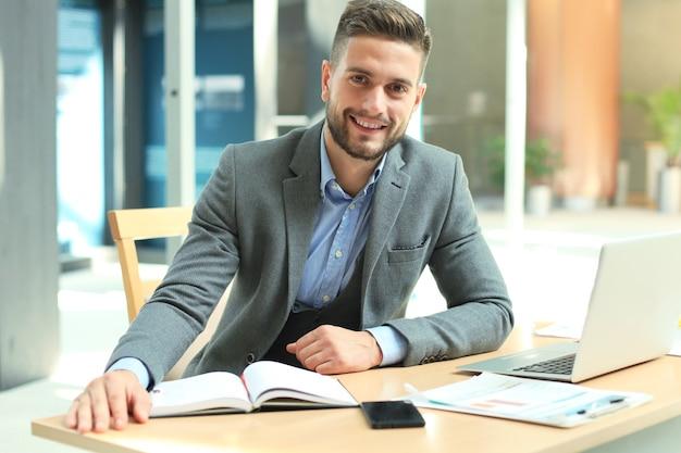 Portrait d'homme d'affaires heureux assis au bureau, regardant la caméra, souriant.