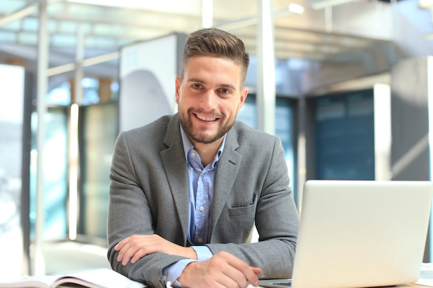 Portrait d'un homme d'affaires heureux assis au bureau, regardant la caméra en souriant.