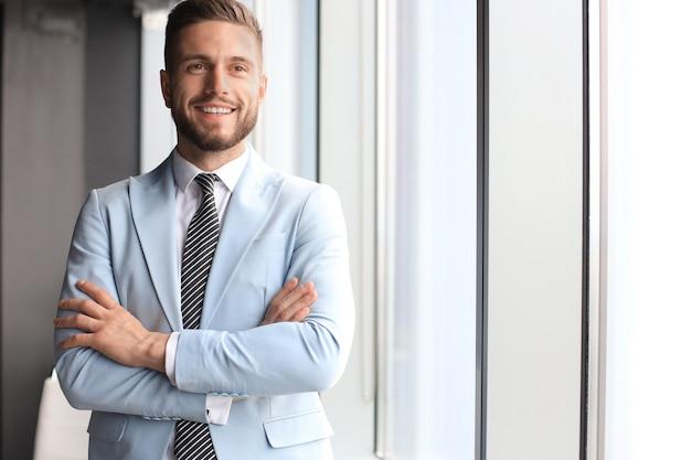Portrait d'homme d'affaires heureux avec les bras croisés debout au bureau.
