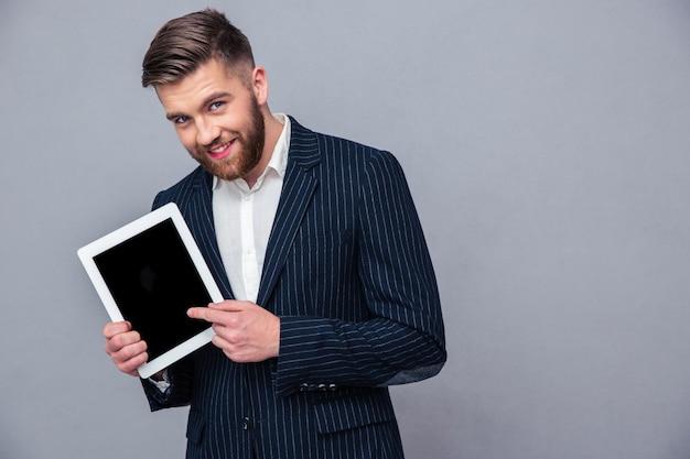 Portrait d'un homme d'affaires heureux montrant l'écran de l'ordinateur tablette sur mur gris
