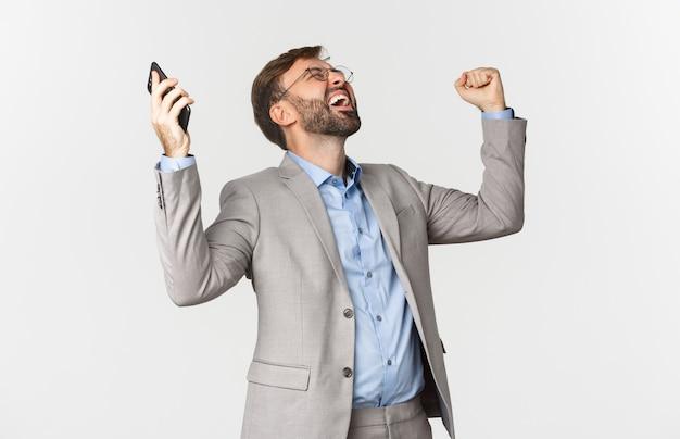 Portrait d'homme d'affaires heureux et soulagé, tenant le smartphone, levant les mains