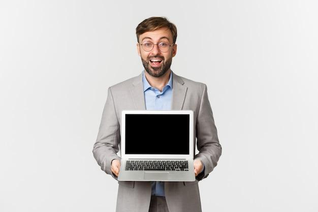 Portrait d'homme d'affaires heureux souriant avec barbe, portant des lunettes et costume