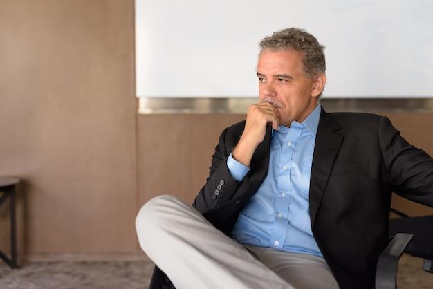 Portrait d'homme d'affaires hispanique beau mature à l'immeuble de bureaux à l'intérieur