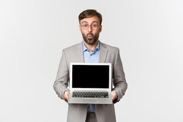 Portrait d'homme d'affaires impressionné avec barbe, portant des lunettes et un costume