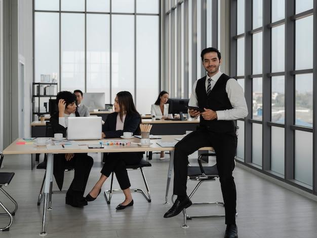 Portrait d'un homme d'affaires intelligent tenant une tablette et le pouce vers le haut avec des personnes travaillant au bureau, le succès de l'équipe commerciale, l'analyse et le concept de stratégie