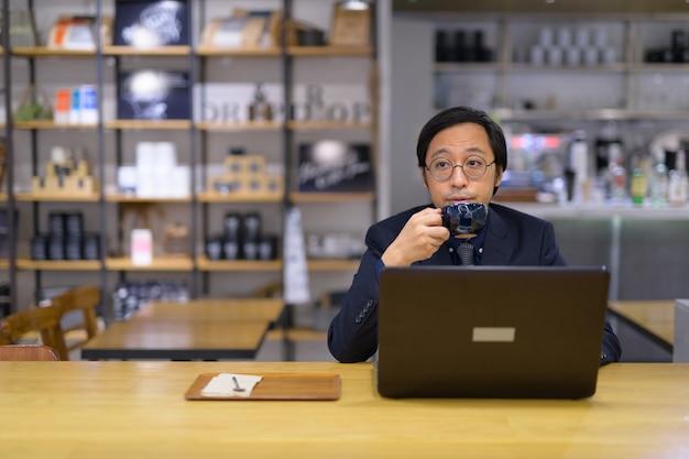 Portrait d'homme d'affaires japonais assis à l'intérieur du café