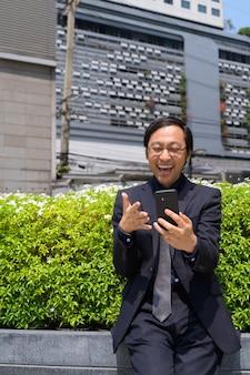 Portrait d'homme d'affaires japonais prendre l'air frais avec la nature dans la ville en plein air