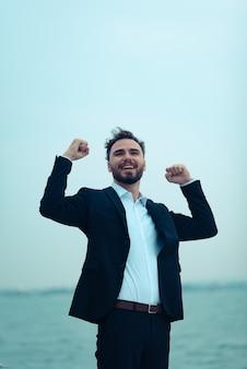 Portrait d'homme d'affaires de jeune homme souriant élégant en costume posant sur un yacht