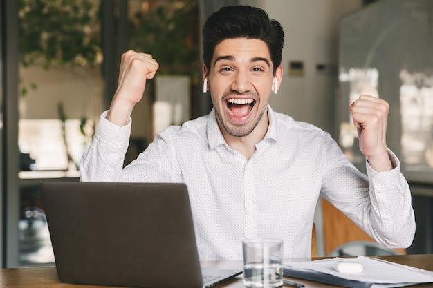 Portrait d'homme d'affaires joyeux de 30 ans portant une chemise blanche et des écouteurs sans fil criant et serrant les poings comme gagnant, alors qu'il était assis au bureau