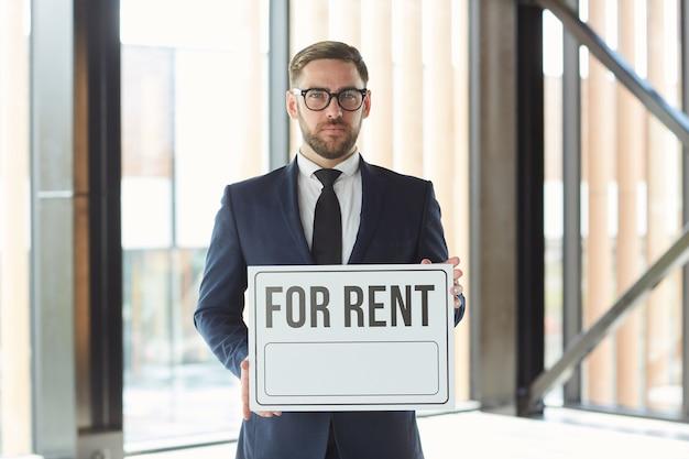 Portrait d'homme d'affaires mature en costume tenant une pancarte à louer