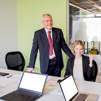 Portrait d'un homme d'affaires mature et femme d'affaires au lieu de travail