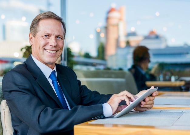 Portrait d'un homme d'affaires mature heureux à l'aide de tablette numérique au restaurant