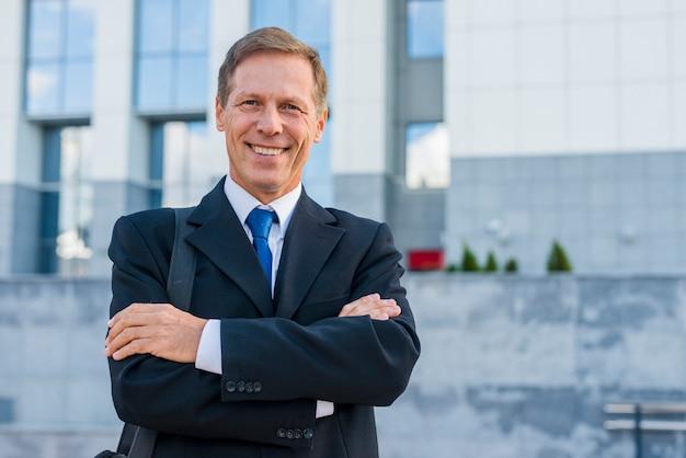 Portrait d'un homme d'affaires mature heureux avec les bras croisés