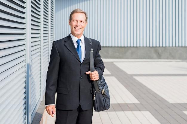 Portrait d'un homme d'affaires mature heureux avec sac à main
