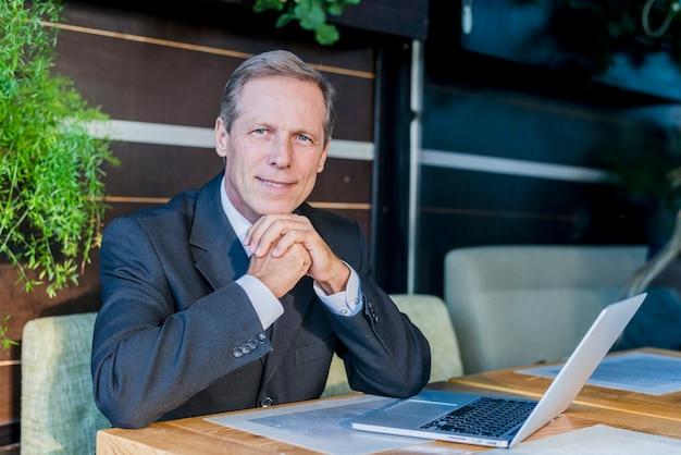 Portrait d'un homme d'affaires mature avec un ordinateur portable sur un bureau au restaurant
