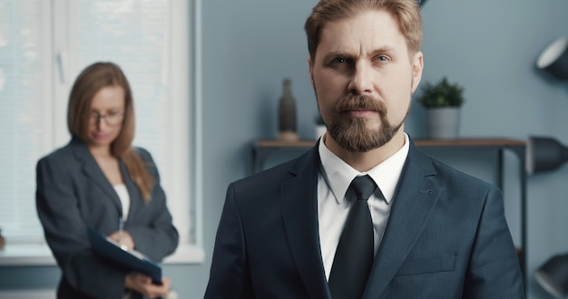 Portrait d'homme d'affaires mature sérieux avec sa collègue de travail sur fond de bureau