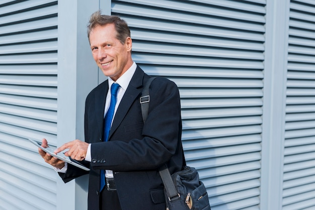 Portrait d'un homme d'affaires mature souriant à l'aide de tablette numérique