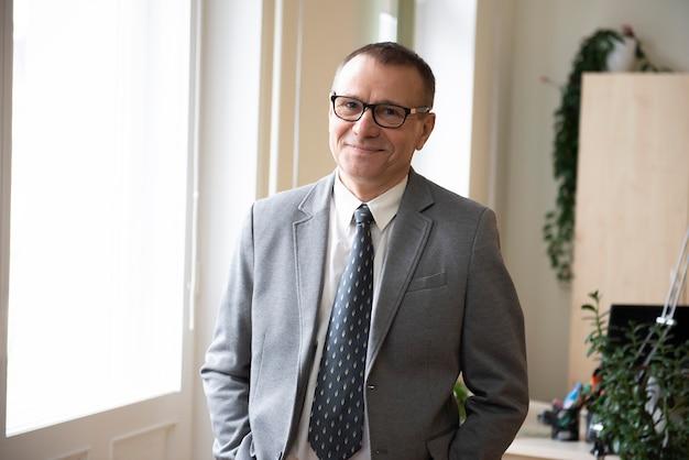 Portrait d'homme d'affaires mature souriant confiant debout à la fenêtre au bureau