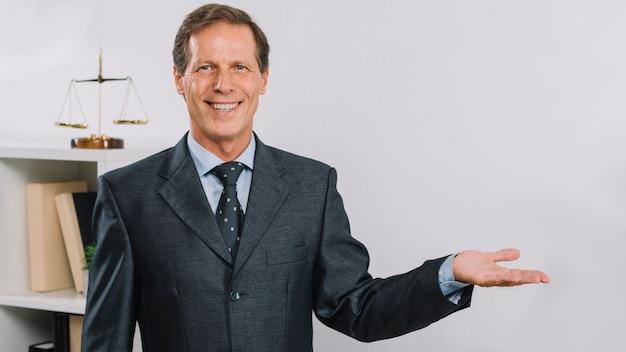 Portrait d'un homme d'affaires mature souriant présentant