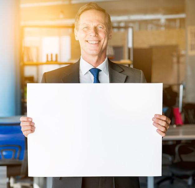 Portrait d'un homme d'affaires mature souriant tenant une pancarte blanche