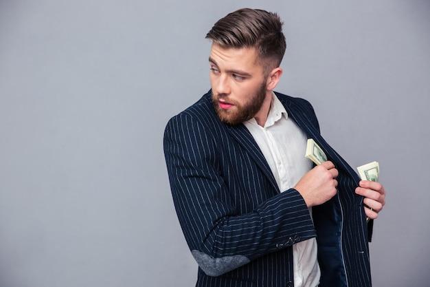 Portrait d'un homme d'affaires mettant de l'argent dans la veste et à la recherche de suite sur un mur gris