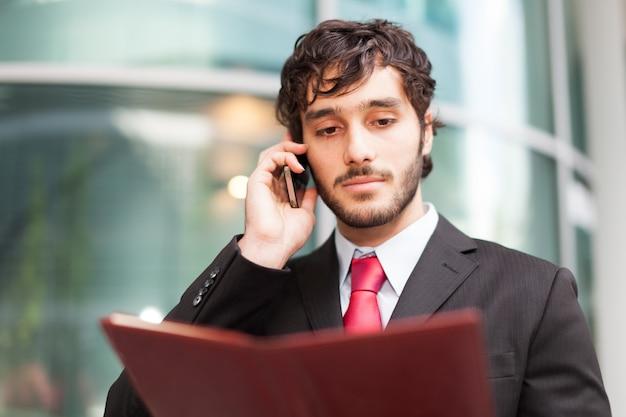 Portrait d'un homme d'affaires occupé en utilisant son téléphone portable tout en tenant un agenda