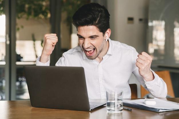 Portrait d'homme d'affaires prospère de 30 ans portant une chemise blanche et des écouteurs bluetooth hurlant et serrant les poings, tout en regardant un ordinateur portable au bureau