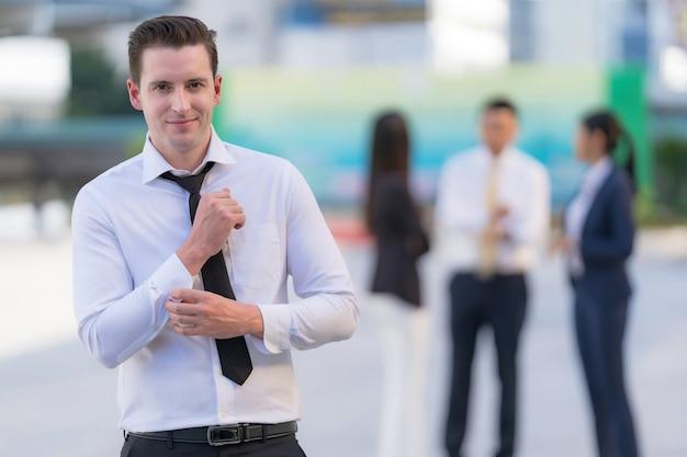 Portrait d'homme d'affaires prospère debout devant des immeubles de bureaux modernes