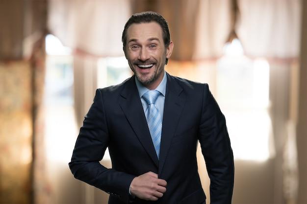 Portrait d'homme d'affaires qui rit. homme positif debout à l'intérieur dans un restaurant ou un hôtel. vêtu d'un costume sombre.