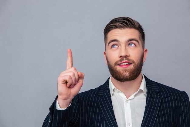 Portrait d'un homme d'affaires réfléchi, pointant le doigt vers le haut sur un mur gris