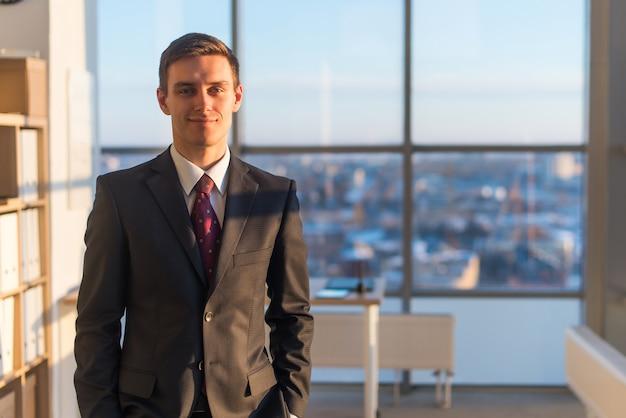 Portrait d'homme d'affaires, regardant la caméra, debout au bureau.