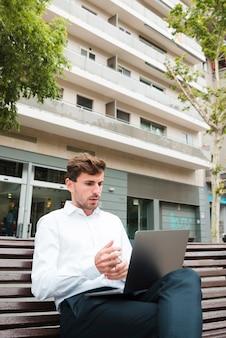 Portrait, de, a, homme affaires, regarder sérieusement, ordinateur portable, devant, bâtiment