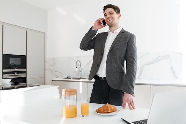 Portrait d'un homme d'affaires réussi parlant sur téléphone mobile tout en prenant son petit déjeuner et en travaillant sur un ordinateur portable à la maison