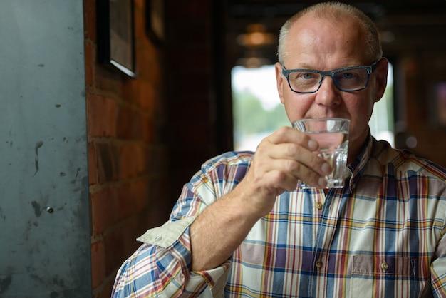 Portrait d'homme d'affaires senior de l'eau potable au café