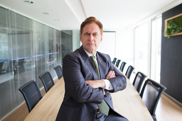 Portrait d'un homme d'affaires senior sévère dans la salle de réunion