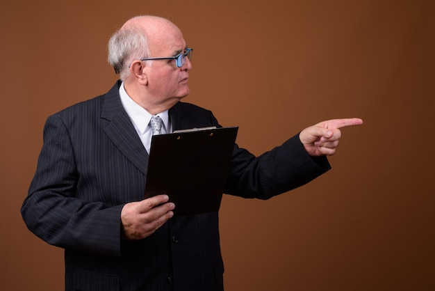 Portrait d'homme d'affaires senior en surpoids avec presse-papiers