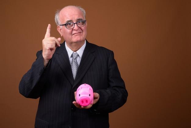 Portrait d'homme d'affaires senior en surpoids tenant tirelire