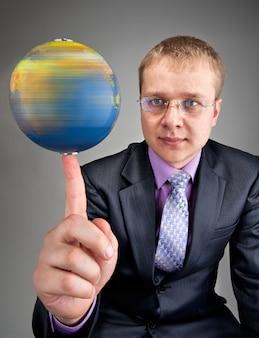 Portrait d'homme d'affaires sérieux faisant tourner le globe terrestre sur le doigt