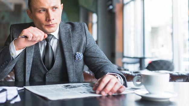 Portrait d'un homme d'affaires sérieux avec un journal en détournant les yeux