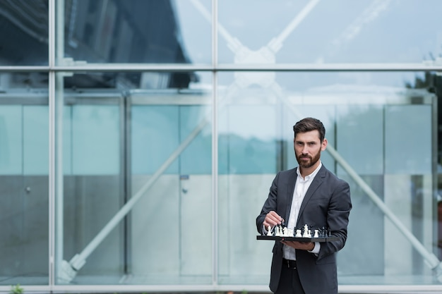 Portrait d'un homme d'affaires sérieux réussi tenant un échiquier avec des échecs dans ses mains propose de faire un pas