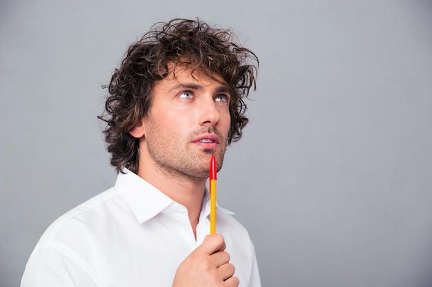 Portrait d'un homme d'affaires songeur avec un stylo à la recherche sur mur gris