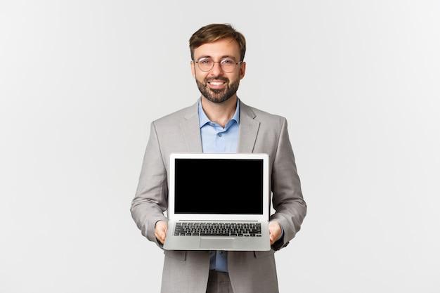Portrait d'homme d'affaires souriant avec barbe, portant des lunettes et costume