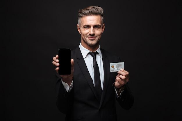 Portrait d'un homme d'affaires souriant et confiant vêtu d'un costume formel tenant un téléphone portable et une carte de crédit isolé sur un mur noir