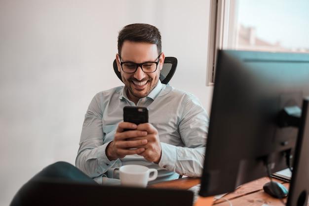 Portrait d'un homme d'affaires souriant heureux à lunettes à l'aide de smartphone tout en étant assis au bureau.