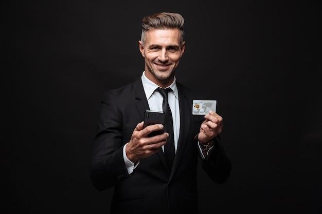 Portrait d'un homme d'affaires souriant et mal rasé vêtu d'un costume formel tenant un téléphone portable et une carte de crédit isolé sur un mur noir