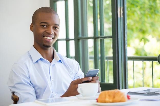 Portrait d'homme d'affaires souriant tenant un téléphone mobile au restaurant