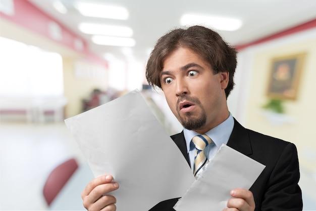 Portrait d'homme d'affaires stressé avec des papiers